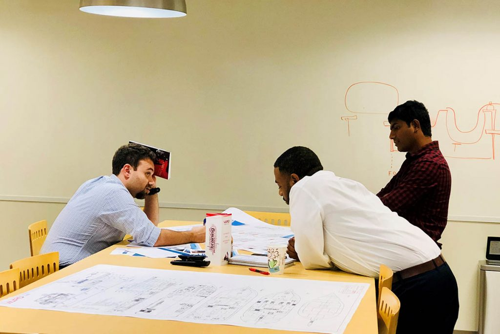 Vard Marine Houston naval architects, three employees discussing project drawings