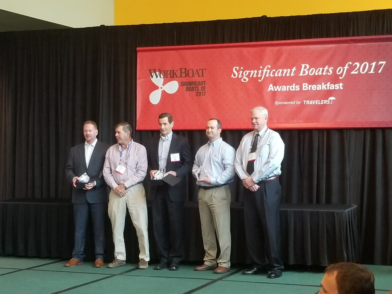 WorkBoat Show Awards Ceremony 2017, five men including Bill Lind, VP Vard Marine Houston standing in front of Significant Boats of 2017 Awards Breakfast red banner