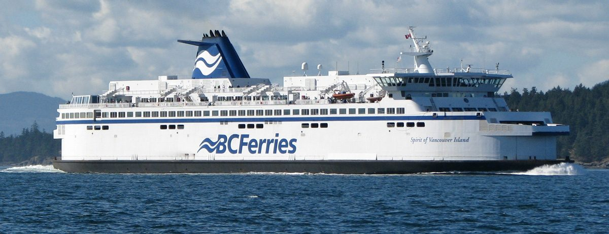 BC Ferries Spirit of Vancouver Island  sailing past BC coast with trees and mountains in background