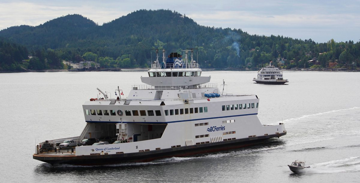 BC Ferries Queen of Cumberland sailing past an island with another ferry in the distance and small boat alongside