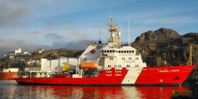 Canadian Coast Guard CCGS Lenoard J Cowley fisheries patrol vessel in water moving past a port