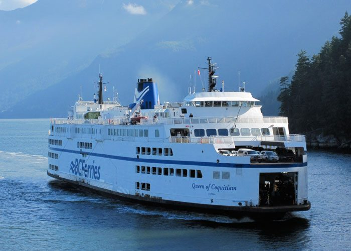 MV BC Ferries design Queen of Coquitlam design by Vard Marine sailing past trees and mountains