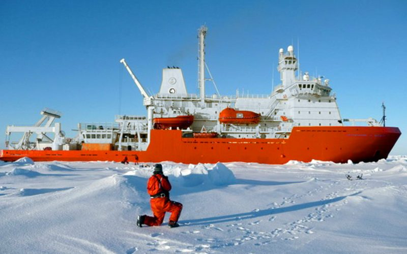 Nathaniel B. Palmer icebreaker research vessel in ice while scientist/man kneels down infront